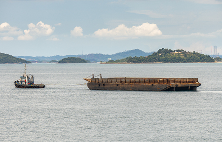 Tug boat tows bulk cargo lighter barge along Singapore strait near Indonesia shore with small islands in the background.