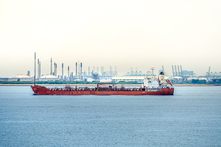Red coloured hull large tanker sails along the coastal of industry port with large petroleum tank farm behide.