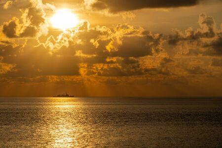 La silhouette d'un navire de guerre peut-être une frégate ou un destroyer navigue le long de la route commerciale pour protéger les ressources nationales des activités illégales en mer la veille du coucher du soleil. Banque d'images