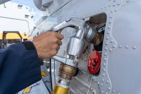 close up of the helicopter refueling  operation onboard the navy ship while the ship is underway at sea