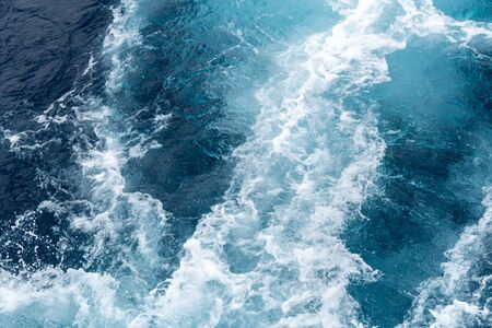 Wave created by ship sails pass through the sea water. Turbulance flow of sea water happen by the ship moving.