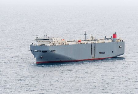 Duże szare statki typu roll-on / roll-off (RORO lub ro-ro) lub statek do przewozu pojazdów oceanicznych zakotwiczają na otwartym morzu. Statek Roro przeznaczony do przewozu ładunków kołowych, takich jak samochody, ciężarówki, przyczepy itp.