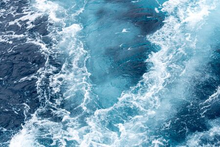 Wave create by ship sails pass through the sea water. Turbulance flow of sea water happen by the ship moving.