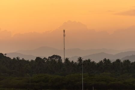 Beautiful sunset scenic of moutain and coconut woods in suburb of Thailand with telecommunication pole in the middle of the photo.