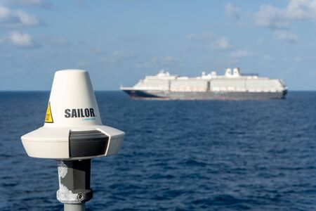 GULF OF SIAM, THAILAND - FEBUARY 12, 2020: SAILOR COBHAM INMARSAT Mini-C transceiver antenna onboard the vessel with large cruise ship in the background.
