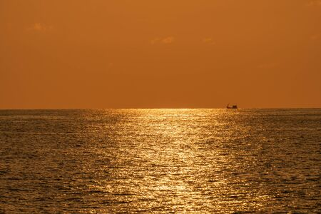 Fishing boat sails along the sea in the evening before sunset. Silhouette view.