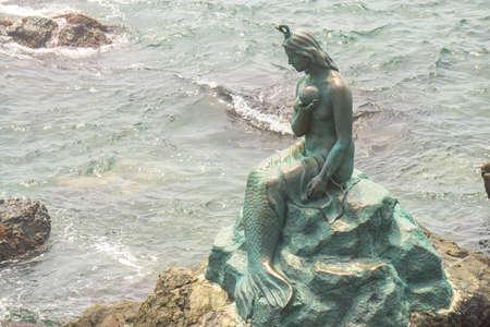 The bronze mermaid statue locate at the rock beach of Haeundae Dongbaekseom Island near Haehundae beach.