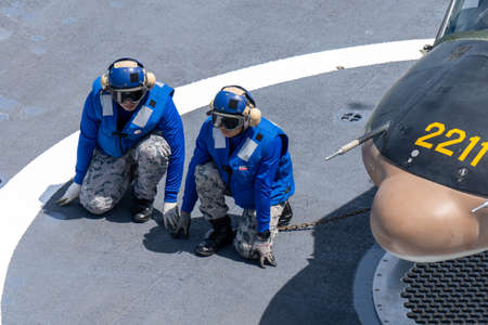 CHONBURI, THAILAND - JULY 9, 2020: Members of the tie-down team ties down the Bell 212 helicopter of royal Thai navy on the flight deck of HTMS. Bhumibol Adulyadej and wait for the next order.
