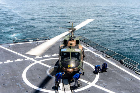 CHONBURI, THAILAND - JULY 9, 2020: Ship's crew release chalks and chains that ties down the Bell 212 helicopter of royal Thai navy on the flight deck of HTMS. Bhumibol Adulyadej.
