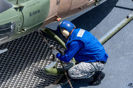 CHONBURI, THAILAND - JULY 9, 2020: Ship's crew ties down the Bell 212 helicopter of royal Thai navy on the flight deck of HTMS. Bhumibol Adulyadej. 新闻类图片