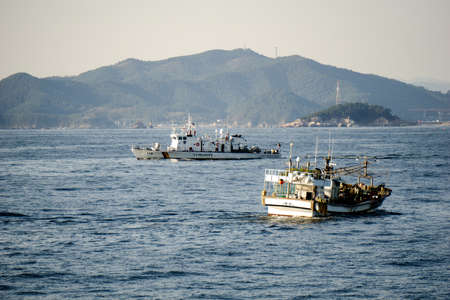 GEOJE, SOUTH KOREA - OCTOBER 20, 2018: Haenuri Class hull number 116, The South Korea coast guard patrol boat sails pass the fishing boat near Geoje Island coast. Redakční