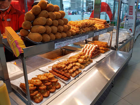 BUSAN, SOUTH KOREA - NOVEMBER 16, 2017: Snack shop sells popular snack made of sausages, Tteok-bokki and other meal coated with flour and fried.