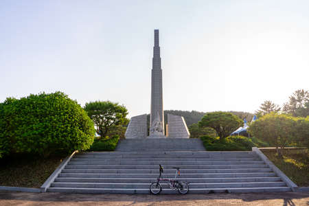 GEOJE, SOUTH KOREA - JUNE 14, 2017 : Brompton folding bike parks in front of the monument of Admiral Yi Sun-Sin at Okpo great vitory commemoative park