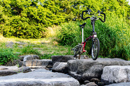 GEOJE, SOUTH KOREA - JUNE 15, 2017: Brompton folding bike park in front of the small stream in the suburb of South Korea. Redakční