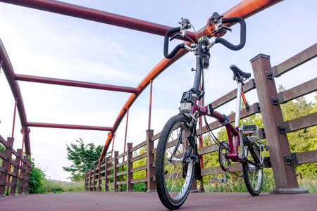 GEOJE, SOUTH KOREA - JUNE 15, 2017: Brompton folding bike parks on the suspension bridge across  small stream in the suburb of South Korea. Redakční