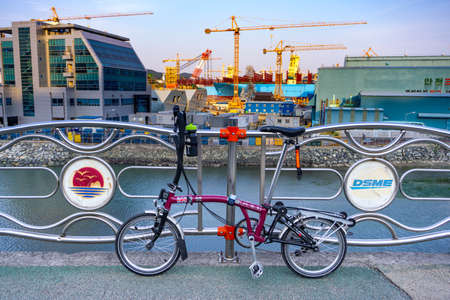 GEOJE, SOUTH KOREA - JUNE 15, 2017: Brompton folding bike parks on the street across DSME shipbuilder in Okpo, Geoje island, South Korea.