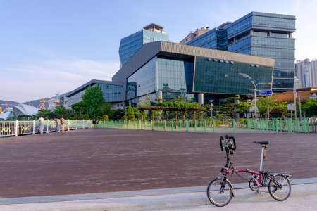 GEOJE, SOUTH KOREA - JUNE 15, 2017: Brompton folding bike parks on the street across DSME shipbuilder headquarter in Okpo, Geoje island, South Korea.