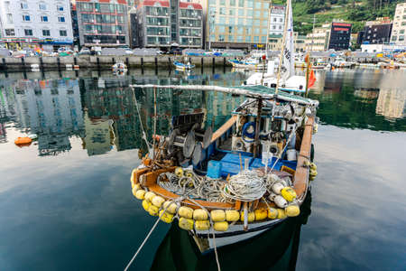 GEOJE, SOUTH KOREA - JUNE 15, 2017: Small fishing boat moors at the pier in DSME harbour in Okpo, Geoje Island, Gyeongsangnam-do, South Korea. Redakční