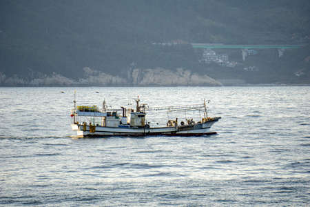 Korean fishing boat sails pass shore line in the internal waters territory. Archivio Fotografico