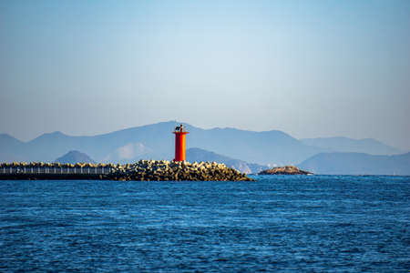 Red beacon on the tip of tetrapod breakwater in the bay of Okpo in Okpo, Gyeongsangnam-do,South Korea.