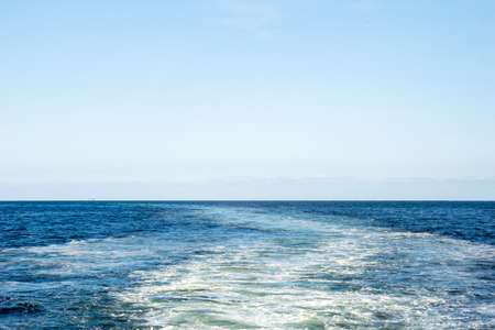Wake of water created by ship that sailing through the calm sea water.
