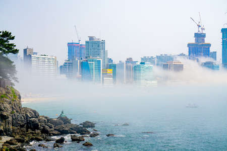 BUSAN,SOUTH KOREA - JULY 20, 2017:  The famous Haehundae beach and bay with thick large mist blow from the sea to the land and pass through skyscrapers in the area.