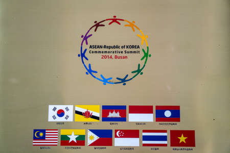 BUSAN,SOUTH KOREA - JULY 20, 2017: Symbol of ASEAN-Republic of Korea Commemorative Summit 2014,Busan and ASEAN countries flags hang on the wall in APEC House.Text under the flags are countries name. Redakční