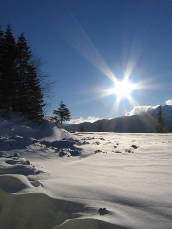 Snow glade and sun bearns on blue sky. Caucasus, Russia Stock Photo - 370142
