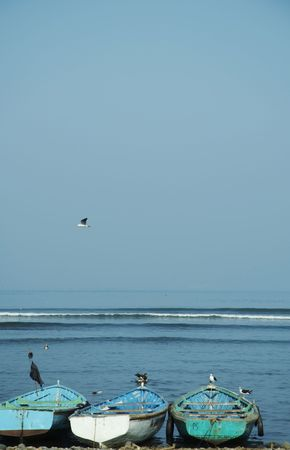 Three blue boat in on the Pacific ocean coast photo