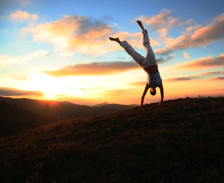 Acrobatic girl on grassland of sunset Stock Photo - 662188
