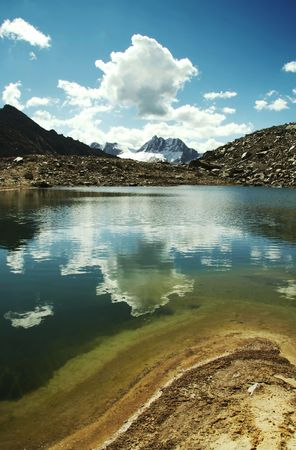 Blue lake and white clouds in Cordilleras mountain photo