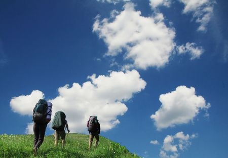 Three tourist going up along grassland photo