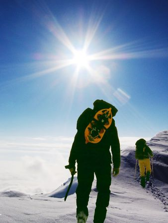 Two climbers going up in snowy slope Stock Photo