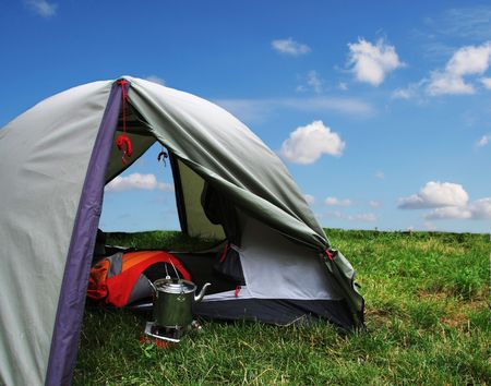 camping equipment: Tent and camping equipment on the green grass