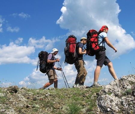 group travel: Three climbers going about stone