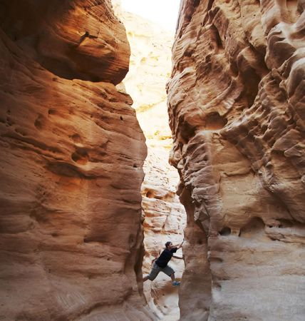slot canyons: girl climbing in the canyon walls
