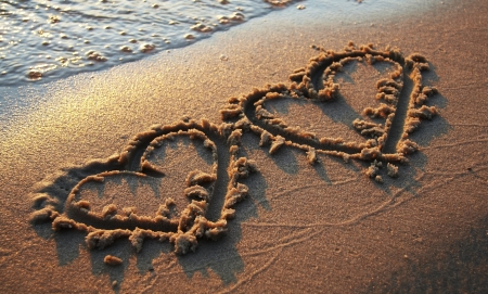 anniversary beach: Two hearts on sand Stock Photo