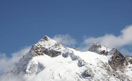 Snowcowered high cordillera mountain and clouds photo