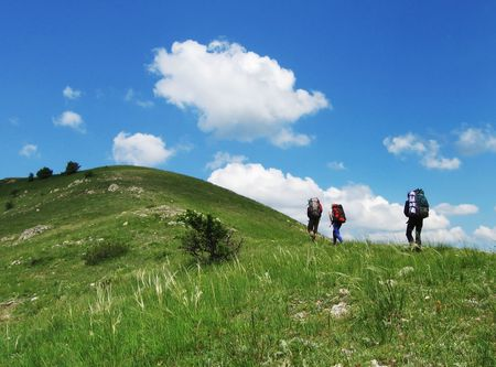 Three climbers going about green hills Stock Photo - 773079