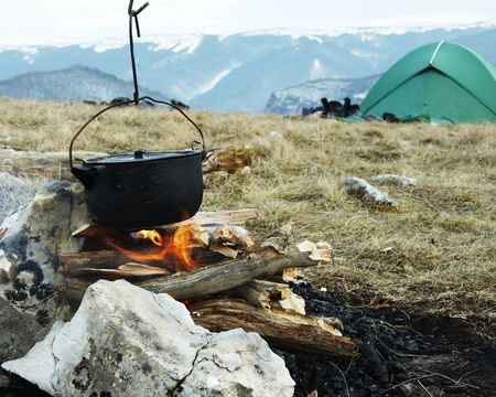 Campfire,kitchenware and tent in camping photo