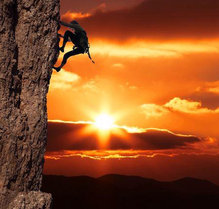 登る: 女の子が登っている夕日を背景に岩の上