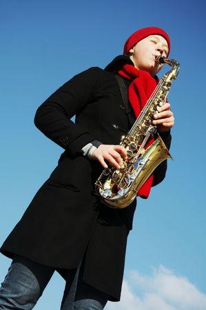 Beautiful girl plays on a saxophone photo