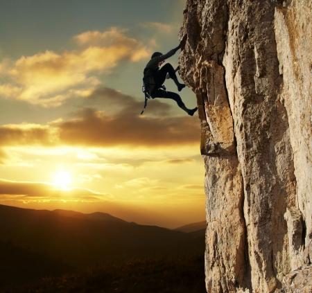 climbing: Ni�a de escalada en roca en la puesta de sol de fondo