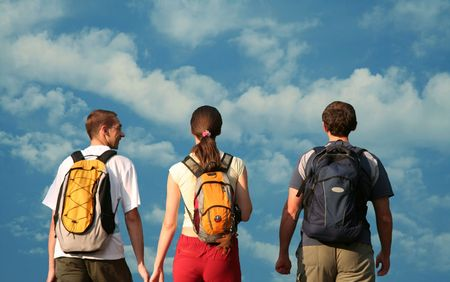 backpackers: Young people going on blue background Stock Photo