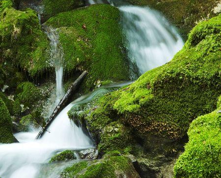 Beautiful small waterfull in green stone photo