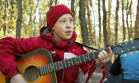 girl playing guitar: Girl playing guitar in forest Stock Photo