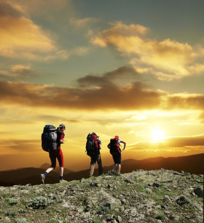 Groep gaat langs heuvel op zonsondergang