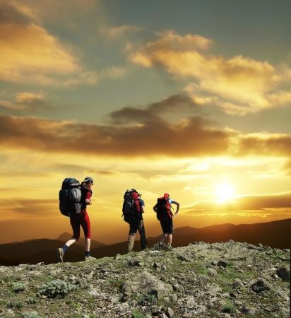 senderismo: Grupo de ir a lo largo de la puesta de sol en la colina