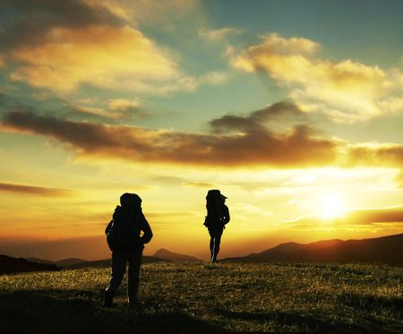 Couple going along hill on sunset photo