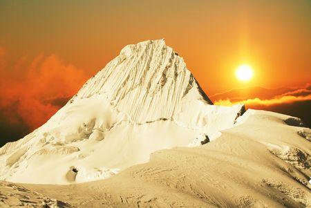 Alpamayo peak in Cordilleras mountain on sunset